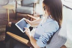 使用触摸板的年轻美丽的女学生在现代coworking的地方 工作在她的数字式片剂的自由职业者女孩 免版税图库摄影