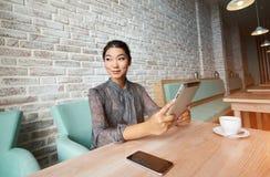 使用触摸板的愉快的韩国女性在咖啡休息期间在餐馆 库存图片