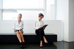 使用触摸板的成功的妇女律师,当她的坐近在办公室内部时的不满意的雇员, 图库摄影