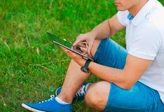 使用触摸板的年轻人外面 免版税图库摄影