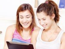 使用触摸板计算机的二个愉快的十几岁的女孩 免版税库存照片