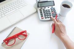 使用计算器和便携式计算机在白色的女商人 免版税库存照片