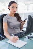 使用计算器和写的懊恼女实业家 免版税库存图片