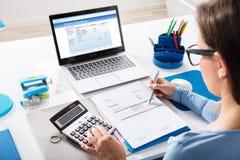 使用计算器的女实业家计算的发货票 免版税库存图片