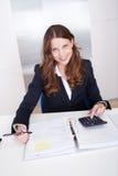 使用计算器的女实业家 免版税库存图片