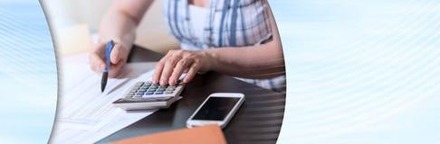 使用计算器的女性会计;全景横幅 库存照片