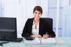 使用计算器的确信的女实业家在办公桌 免版税库存照片