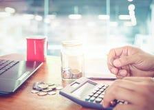 使用计算器的年轻商人财务、税和挽救金钱的 免版税图库摄影