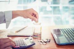 使用计算器的年轻商人财务、税和挽救金钱的 免版税库存照片