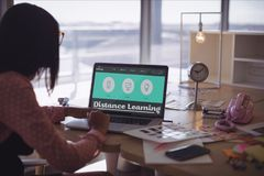 使用计算机人的妇女拿着有电子教学信息的一个电话在屏幕 免版税图库摄影