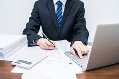 使用计算机会计结算的商人 免版税图库摄影