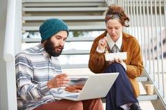 使用计算机和吃午餐的行家夫妇户外 库存图片