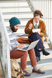 使用计算机和吃午餐的行家夫妇户外 免版税库存图片