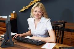 使用计算机和电话的旅馆接待员 免版税图库摄影