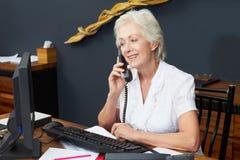 使用计算机和电话的旅馆接待员 免版税库存照片