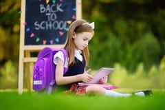使用计算机片剂的可爱的小女孩,当坐一棵草在夏日时 免版税图库摄影