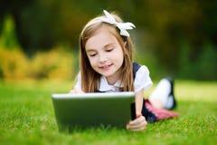 使用计算机片剂的可爱的小女孩,当坐一棵草在夏日时 免版税库存图片