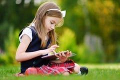 使用计算机片剂的可爱的小女孩,当坐一棵草在夏日时 库存照片