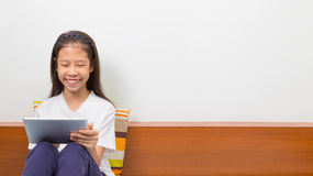 使用计算机片剂的愉快的微笑的亚裔女孩 库存图片
