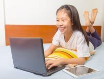 使用计算机片剂的愉快的微笑的亚裔女孩 库存照片