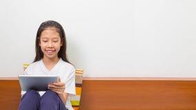 使用计算机片剂的愉快的微笑的亚裔女孩 免版税库存照片