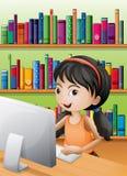 使用计算机的一个女孩在图书馆 免版税库存照片