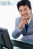 使用计算机的一个愉快的经理的纵向 免版税库存照片