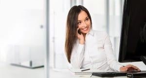 使用计算机的一个年轻女商人的画象在办公室 免版税库存照片