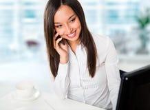 使用计算机的一个年轻女商人的画象在办公室 图库摄影