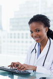 使用计算机的一位微笑的女性医生的画象 免版税库存图片
