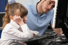 使用计算机的不快乐的教师和女孩在选件类 库存照片