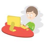 使用计算机的不快乐的男孩。 免版税库存照片
