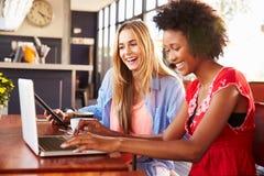 使用计算机的两名妇女在咖啡店 免版税库存照片
