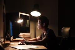 使用计算机的严肃的人和输入暗室 库存照片