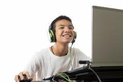使用计算机的亚裔少年和听到与兴高采烈的fac的音乐 库存图片