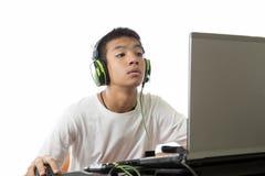 使用计算机的亚裔少年和听到音乐 库存图片