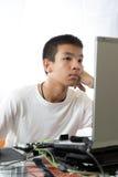 使用计算机的亚裔少年 免版税库存图片
