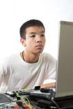 使用计算机的亚裔少年 免版税库存照片