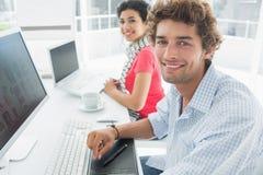 使用计算机的偶然夫妇在办公室 免版税图库摄影