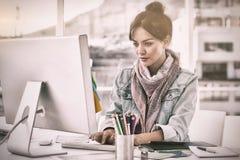 使用计算机的偶然妇女在办公室 免版税库存图片
