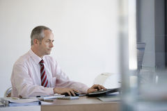 使用计算机的商人在书桌 免版税图库摄影