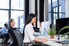 使用计算机的商人运转概念,亚裔女实业家键入的键盘,队在现代繁忙的办公室 库存图片