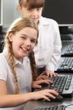 使用计算机的女孩在学校课程 免版税库存照片