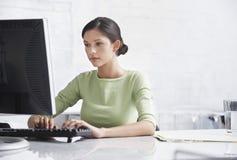 使用计算机的女实业家在书桌 库存图片
