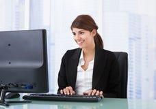 使用计算机的女实业家在办公桌 库存图片