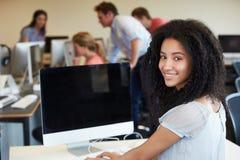 使用计算机的女性大学生在教室 库存照片