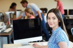 使用计算机的女性大学生在教室 图库摄影