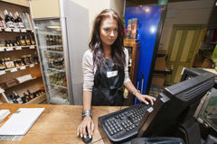 使用计算机的女推销员画象在现金柜台在超级市场 库存照片