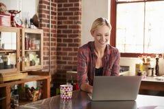 使用计算机的少妇在厨房,关闭在最前面的视图 免版税库存图片