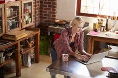 使用计算机的少妇在厨房,大角度 免版税库存图片